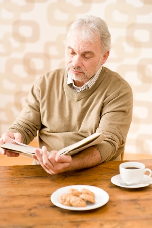 Senior mature man reading book having coffee, cookies at wooden table Stock Photo - 8745746