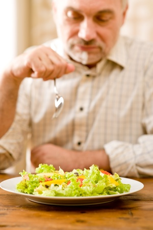 Senior mature man eat vegetable salad at wooden table Stock Photo - 8745742