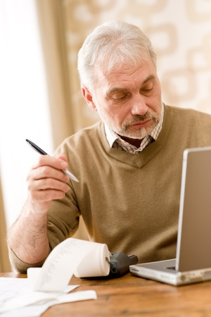 old home office: Senior mature man - home office using paper tape calculator and laptop Stock Photo