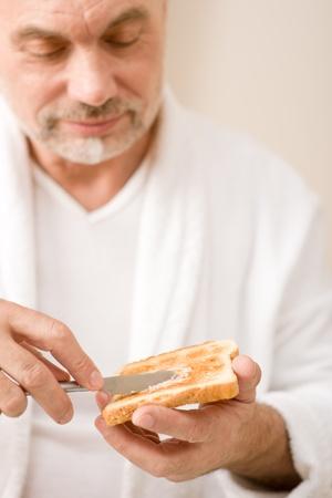 Senior mature man having breakfast butter toast wear bathrobe Stock Photo - 8863186