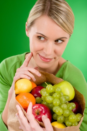 Healthy lifestyle - woman with fruit shopping paper bag on green background Stock Photo - 8863221