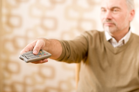 Senior mature man holding remote control in hand Stock Photo - 8863232
