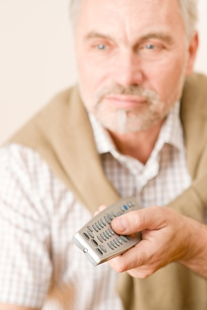 Senior mature man holding remote control in hand photo