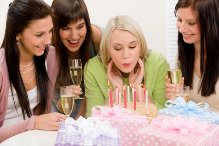 Birthday party - woman blowing candle on cake, champagne, presents photo
