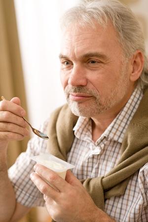 teaspoon: Senior mature man eat yogurt snack holding teaspoon