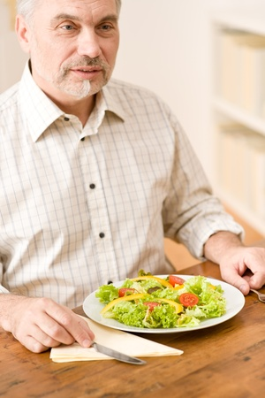 Senior mature man eat vegetable salad at wooden table photo