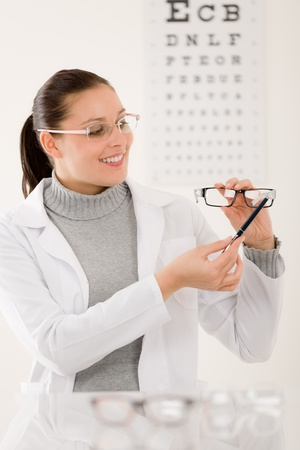 optometrist: Optician doctor woman with prescription glasses and eye chart Stock Photo