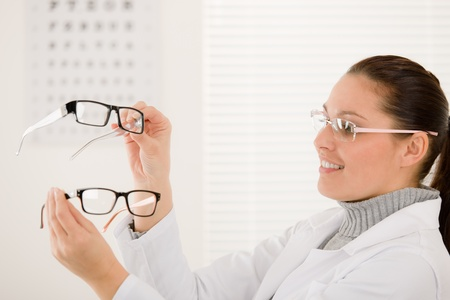 Optician doctor woman with prescription glasses and eye chart photo
