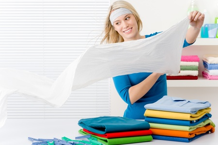 Laundry - woman folding clothes home photo