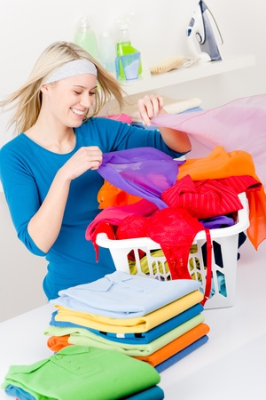 Laundry - woman folding clothes home, housework photo
