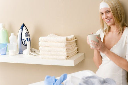 Laundry ironing - woman coffee break after housework photo