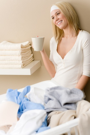folding: Laundry ironing - woman break with drink after housework
