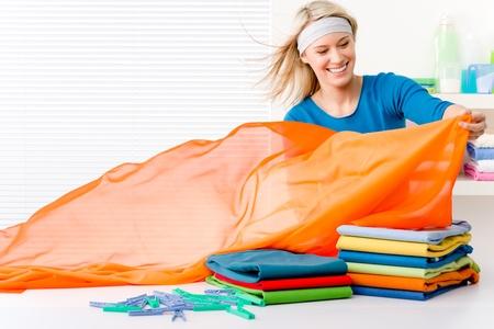 Laundry - woman folding clothes, housework Stock Photo