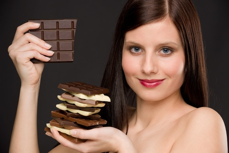 Chocolate - portrait of healthy woman enjoy sweets on black background photo