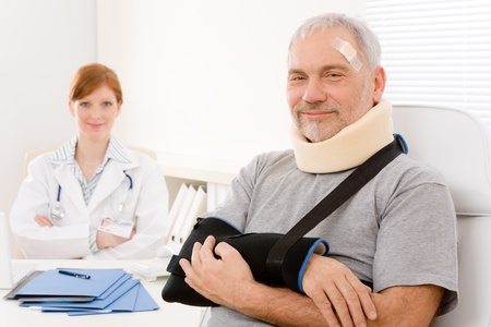 accident at work: Portrait of senior patient with broken arm in doctor office