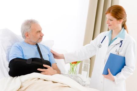 brazo roto: Hospital - doctora examinar senior paciente con fractura de brazo Foto de archivo