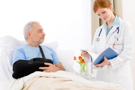 Hospital - female doctor examine senior patient with broken arm Stock Photo