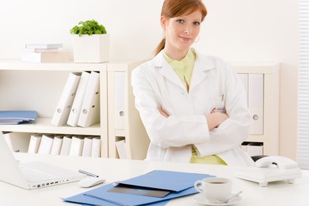 Office uniforms: Consultorio - m�dico femenina retrato sentarse a la mesa