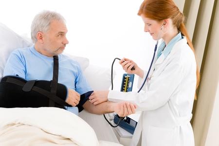 Hospital - doctor measure blood pressure patient with broken arm photo