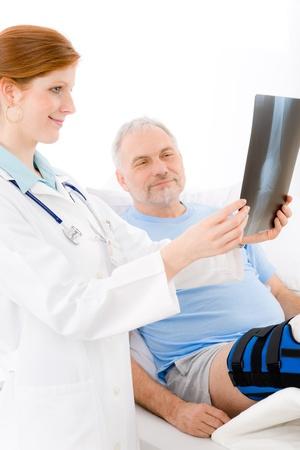 Hospital - female doctor examine x-ray senior patient broken leg photo