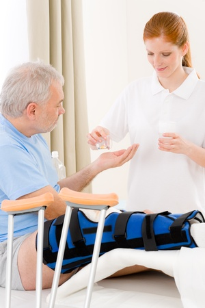 Hospital - female nurse give pill patient with broken leg photo