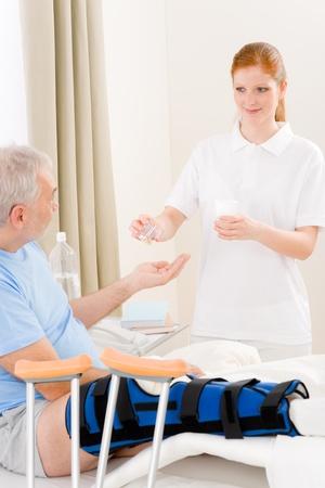 Hospital - female nurse give pill to senior patient with broken leg photo