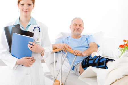 crutches: Hospital - female doctor examine senior patient with broken leg Stock Photo