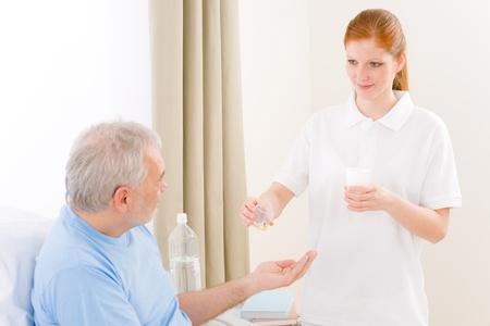 Hospital - female nurse give pill to senior patient Stock Photo - 9248655