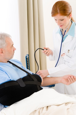 broken arm: Hospital - doctor check blood pressure of patient with broken arm