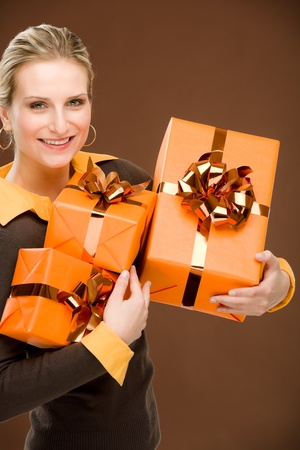 Young happy woman hold birthday present on brown photo