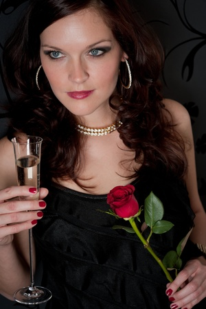 Cocktail party - woman drink champagne hold red rose photo