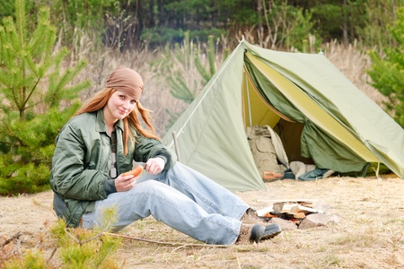 Camping happy woman nature tent cut sausage by fire photo