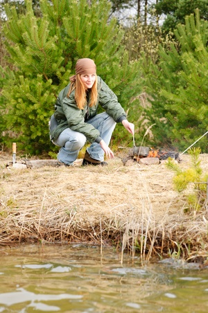 Camping happy woman cook food fire nature water stream photo