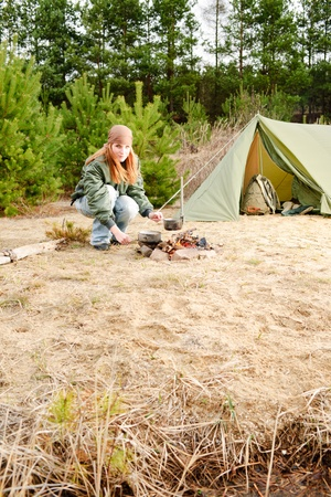 Camping happy woman cook food fire tent nature photo