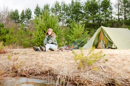 Camping tent happy woman sitting fire nature water photo