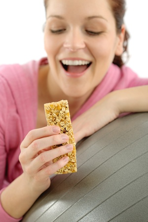 Fitness woman eat cereal bar sportive outfit in gym photo
