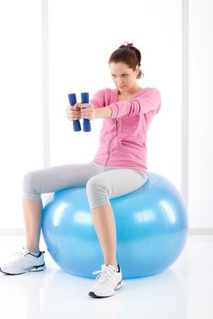 Fitness happy woman exercise dumbbell ball on white Stock Photo - 9331771