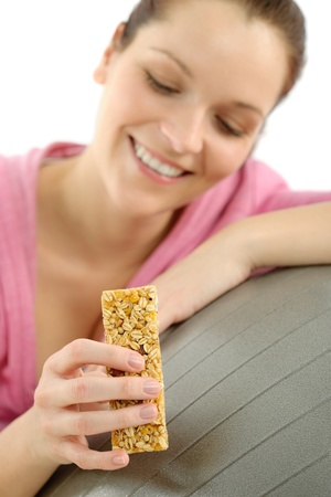 Fitness happy woman eat granola bar sportive outfit in gym photo