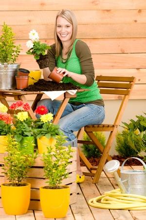 watering garden: Gardening woman hold flowerpot plant spring terrace