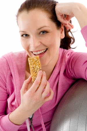 Fitness woman eat granola bar sportive outfit in gym Stock Photo - 9365366