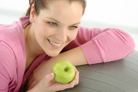 Fitness woman eat apple sportive outfit in gym photo