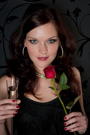 Cocktail party woman drink champagne hold red rose photo