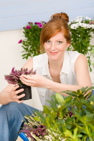 Summer garden terrace redhead woman hold potted flower photo