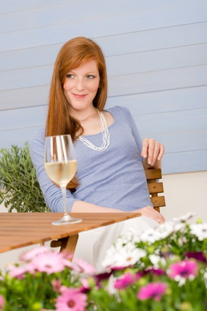 Summer terrace redhead woman hold glass of wine in garden photo