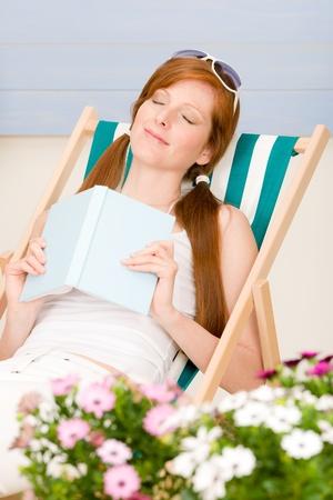 Summer terrace red hair woman relax in deckchair garden photo