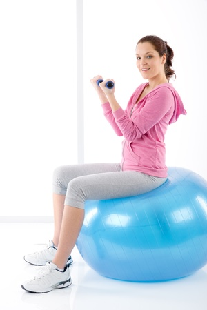 Fitness happy woman exercise dumbbell ball on white Stock Photo - 9410078