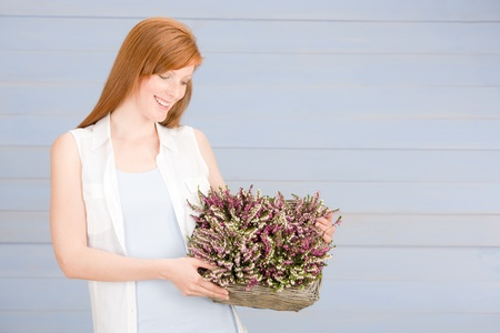 Summer portrait of redhead woman hold basket with flowers photo
