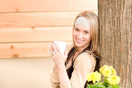 Garden woman terrace enjoy cup of coffee in spring garden