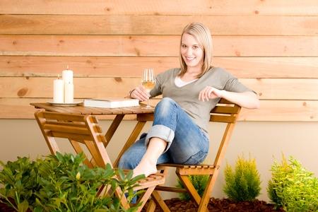 terrace: Garden happy woman enjoy glass of wine sitting on terrace