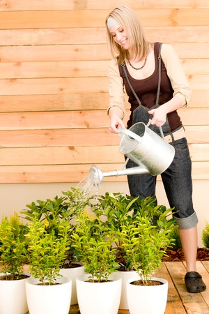 Gardening woman hold watering can plant spring terrace